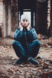 Beautiful young woman sits in ruins on an orange background in a cap and scarf royalty free stock images