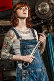 Beautiful redhead mechanic fixing brakes. Photo of a young beautiful redhead mechanic with tattoos and wearing overalls fixing the brakes on a car. Attached Stock Photos