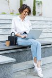 Young beautiful woman sitting outdoors using laptop computer royalty free stock images