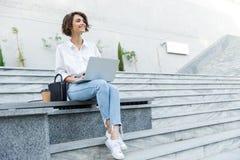 Young beautiful woman sitting outdoors using laptop computer royalty free stock photos