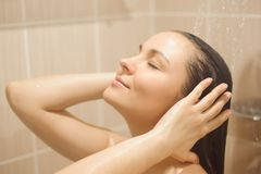 Photo of young beautiful woman taking relaxing shower stock image