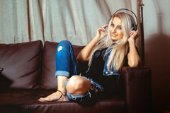 Photo of young beauty woman in casual clothes listening to the m. Usic in headphones. Concept of relax, refreshment and leisure Royalty Free Stock Photography