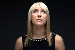 Photo of young blond woman looking up. On black background Stock Image