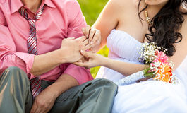 Photo of young bride putting wedding ring on grooms hand Royalty Free Stock Photo