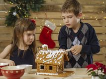 Brother and sister decorating gingerbread house. Photo of a young brother and sister decorating a gingerbread house at home just before Christmas stock photos
