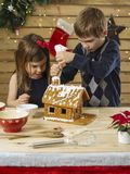 Brother and sister decorating gingerbread house. Photo of a young brother and sister decorating a gingerbread house at home just before Christmas stock photo
