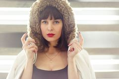 Photo of young brunette in jacket with fur hood stock photos