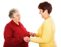 Elderly woman and young caregiver. Photo of young caregiver holding elderly women hands Stock Photo