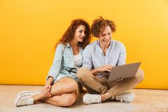 Photo of young content couple man and woman 20s sitting on floor. And using silver laptop isolated over yellow background royalty free stock photos