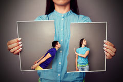 Photo of young couple in quarrel. Woman holding the lacerated photo of young couple in quarrel Stock Images
