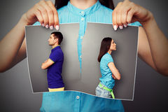 Photo of young couple in quarrel. Woman lacerating photo of young couple in quarrel over dark background Royalty Free Stock Photos