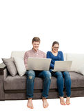 Photo of young couple sitting on couch with laptops Stock Images