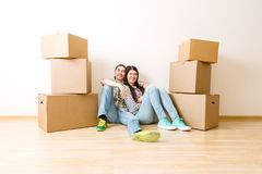 Photo of young couple sitting on floor among cardboard boxes stock photos