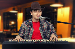 Photo of young cowboy playing the digital piano at pub Stock Photography