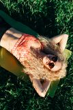 Photo of young curly woman in sunglasses lying on rug in park royalty free stock photo