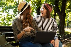 Excited happy ladies friends outdoors sitting using laptop computer. royalty free stock photos