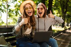 Emotional excited happy ladies friends outdoors sitting using laptop computer showing thumbs up gesture. royalty free stock photos