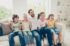 Photo of young father with youngster, youth funky kids big tooth. Y smile, raised hands up sit on comfort, cozy sofa in bright lovely living flat room and look royalty free stock photos