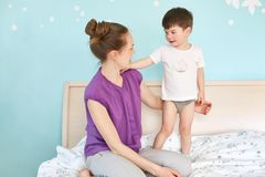 Photo of young female with hair knot looks at her little son who stands near her, tries to make him sleep, sit on bed in bedroom w stock image