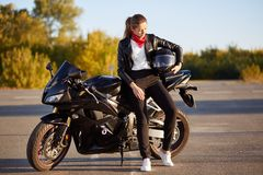 Photo of young female motorcyclist wears fashionable clothes, white sneakers, holds helmet under arm, stands near black motorbike, royalty free stock images