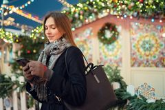 Photo of young girl with phone in hands on winter walk in city royalty free stock photography