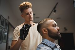 A handsome man is getting a haircut by hairdresser on a barbershop background. An attractive guy in the beauty salon. stock photography