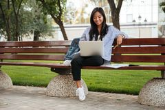 Photo of young happy asian female student relaxing with laptop, Stock Images