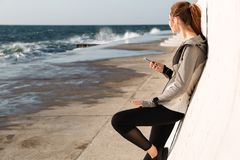 Photo of young healthy sport woman, listening to music while res. Ting after workout, standing near white wall, seaside outdoor Stock Images