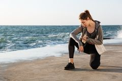 Photo of young healthy sport woman sitting on knee, checking mes. Sage on smartphone, seaside outdoor Stock Photos