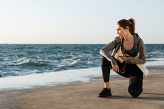 Photo of young healthy sport woman sitting on knee, holding smar. Tphone, looking aside, seaside outdoor Royalty Free Stock Photography