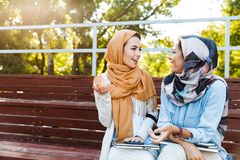 Photo of young islamic girls wearing headscarfs sitting on bench in park and talking. Or discussing royalty free stock images