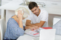 Photo young man helping grandmother managing money Stock Photography
