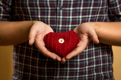 Photo of young man holding red knitted heart in hands Royalty Free Stock Images