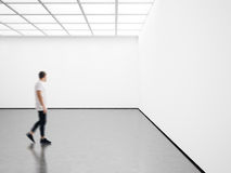Photo of young man in modern gallery looking at the empty canvas. Blank mockup, motion blur Royalty Free Stock Images