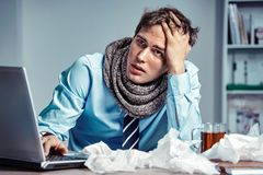 Photo of young man in office suffering virus of flu. Bad feeling. Sick worker has high temperature. Photo of young man in office suffering virus of flu. Medical royalty free stock image
