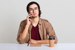 Photo of young man using smart phone for conversaion, discusses ideas for new starup, young hipster male student sitting at whte. Desk, drinking coffee, wearing stock photos