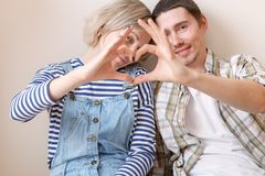 Photo of young married couple with heart from palms sitting on floor among cardboard boxes. In new apartment Royalty Free Stock Image