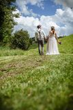 Just married couple walking through the park. Photo of a young newlywed couple walking down a path through a park holding hands Royalty Free Stock Photo