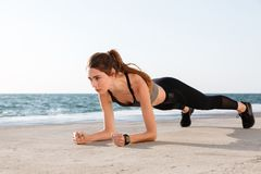 Photo of young pretty female athlete in sport wear standing in a. Plank position at the seaside Stock Photo