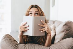 Pretty lady covering face with book. royalty free stock photo