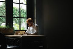 Photo of young readhead bearded man reading a book in cafeteria. Near window Stock Images