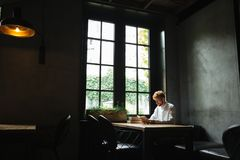 Photo of young readhead bearded man in white shirt reading a boo Royalty Free Stock Photography