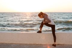 Photo of young slim sport woman tying shoelace at the seaside Stock Images