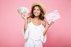 Photo of a young smiling woman in straw hat, holding dollar bill. S and gift box, looking away, isolated on pink background Stock Photos