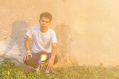 A young Thai boy is squating in front of dirty cement wall in the white shirt and jeans stock photo