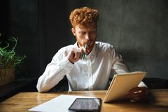 Photo of young thinking readhead bearded man, holding notebook a Stock Photography