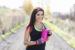 Photo of young woman drinking after running session. Fitness fem. Ale taking a break after workout royalty free stock photos