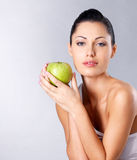 Photo of a young woman with green apple. Stock Photos