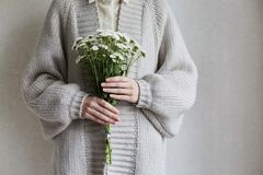Photo of young woman holding white flowers with green stem in her hands royalty free stock images