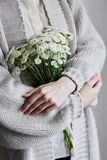 Photo of young woman holding white flowers with green stem in her hands stock images